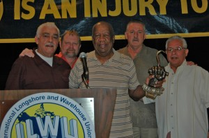 "Honoring George Cobbs: Local 10 pensioner George Cobbs (center) was presented with a bronze hook for his work in establishing the ILWU-PMA Alcohol, Drug and Rehabilitation Program. ""I'm just blessed that I was able to do something in life to help other people,"" Cobbs said. In the photo from left to right are: Coast Committeemen Ray Ortiz, Jr. and Leal Sundet, George Cobbs, ILWU International President Bob McEllrath and Caucus Chair Joe Cortez."