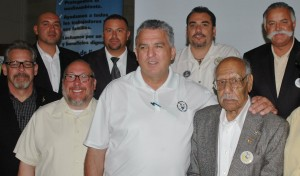 """Surrounded by solidarity: In addition to officials, members and families with young children who attended the Local 56 Convention in San Pedro on July 27, the event featured Felix """"Blacky"""" Alvarez, a 97-year old Local 56 veteran who starred in a short film honoring him and other ILWU """"ship-scalers."""" (L-R) Local 63 President Mike Podue, Local 56 Dispatcher/Business Agent Ruben Hurtado, IBU President Alan Cote, Local 56 President Ilugardo Mendoza, International Vice President (Mainland) Ray Familathe, Local 13 President Chris Viramontes, Local 56 veteran ship scaler Felix """"Blacky"""" Alvarez, and Local 94 President Danny Miranda."""